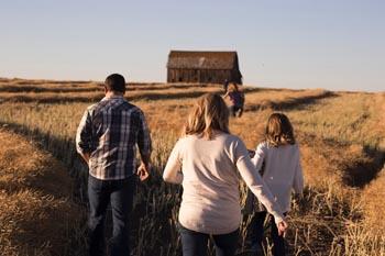 man woman and child walking a wheat field