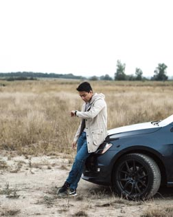 young man in white sweater stranded off road sitting on black vehicle