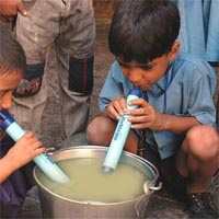 little boys drinking contaminated water with a life straw